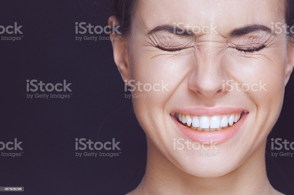 A close-up beauty portrait of a smiling young woman with strongly...