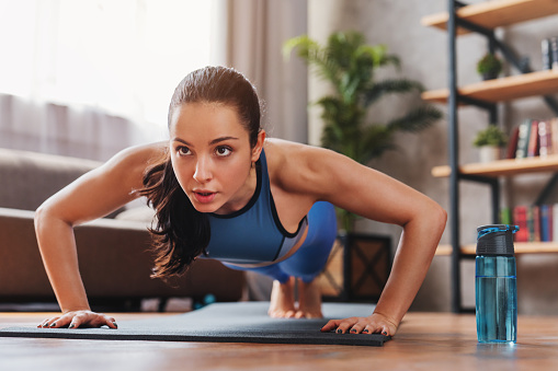 Beautiful young sports lady doing push ups while workout at home