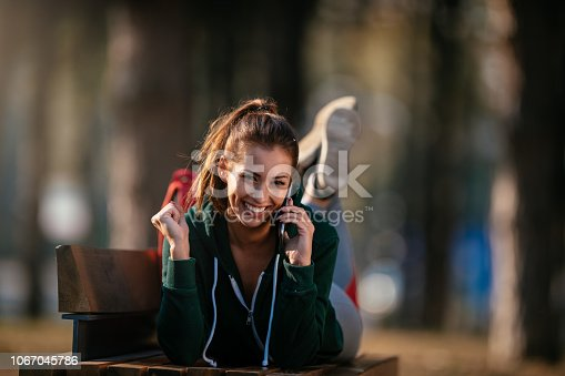 Beautiful young sports woman with smartphone outdoors. Shallow DOF. Developed from RAW; retouched with special care and attention; Small amount of grain added for best final impression. 16 bit Adobe RGB color profile.