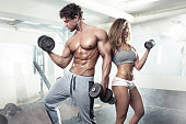 istock beautiful young sporty sexy couple workout in gym 506430620