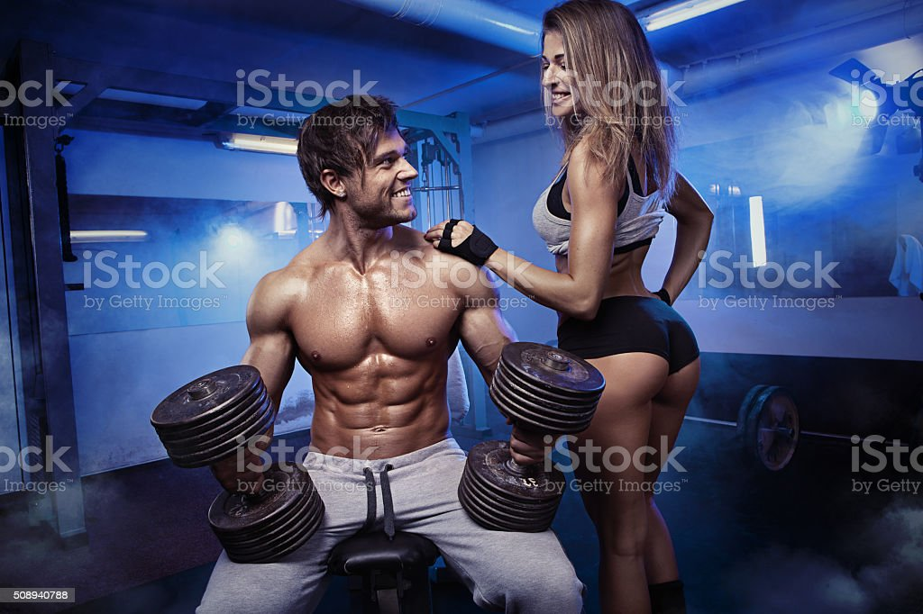 beautiful young sporty sexy couple workout in gym stock photo