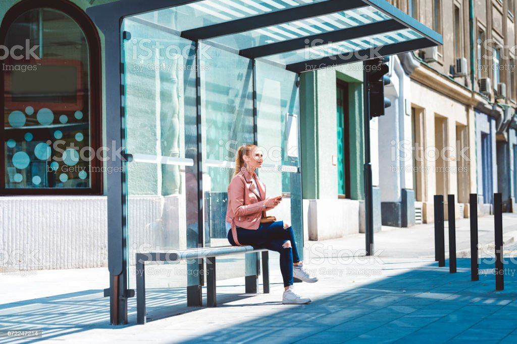 Beautiful young student at the glass made bus shelter stock photo