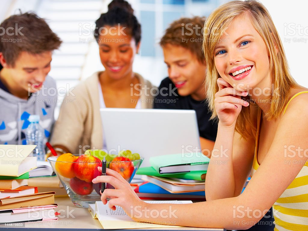 Beautiful young student studying with her friends royalty-free stock photo