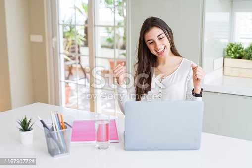 1175468850istockphoto Beautiful young student woman studying for university using laptop and notebook screaming proud and celebrating victory and success very excited, cheering emotion 1167937724