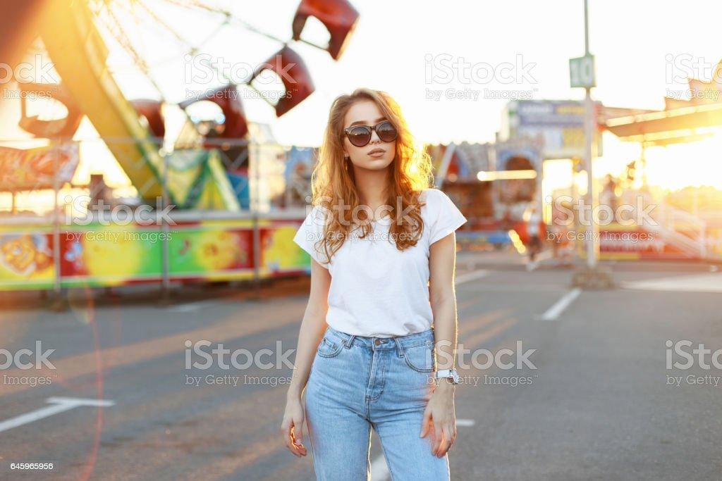 Hermosa joven con estilo en gafas de sol caminando en el parque de atracciones al atardecer. - foto de stock