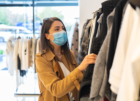 A beautiful young stylish woman with protective face mask is choosing trendy dress in the clothing store during pandemic