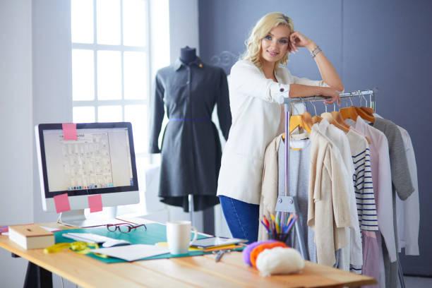 Schöne junge Stylistin in der Nähe von Rack mit Kleiderbügeln in Büro – Foto