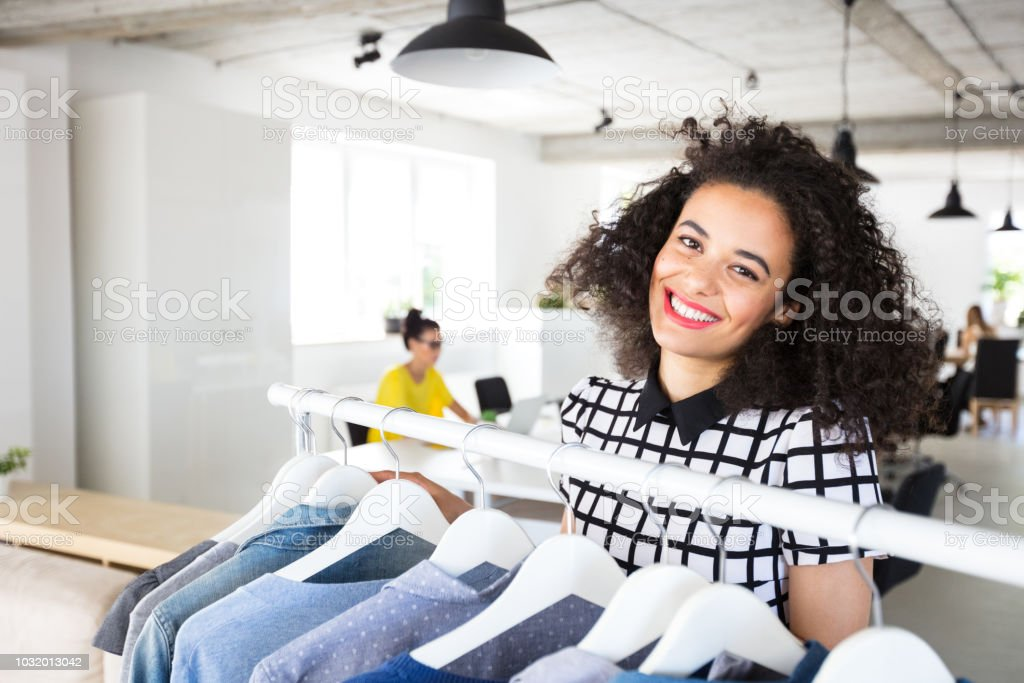 Beautiful young stylist near rack with hangers Portrait of beautiful young female stylist near rack with hangers in design office. Woman with curly hair working in design office. 20-24 Years Stock Photo