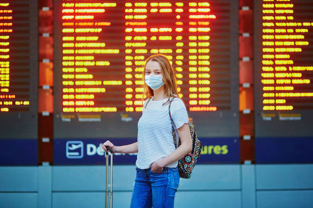 Beautiful young tourist girl with backpack and carry on luggage in international airport stock photo
