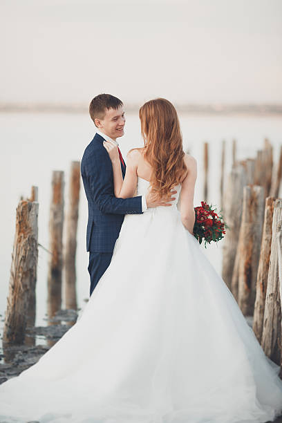 Beautiful young wedding couple, bride and groom posing near wooden stock photo