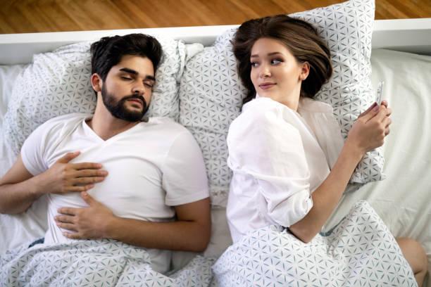 Schöne junge Frau SMS mit Liebhaber auf Smartphone während Mann schläft – Foto