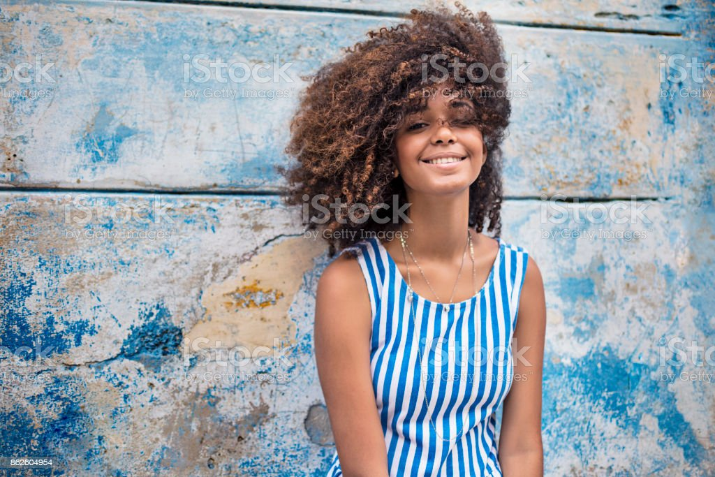 Beautiful young woman against weathered blue wall stock photo