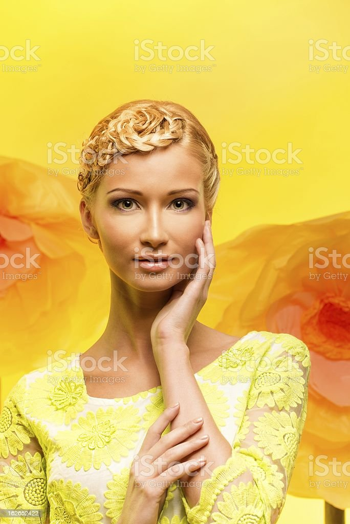 Beautiful young woman among big yellow flowers royalty-free stock photo
