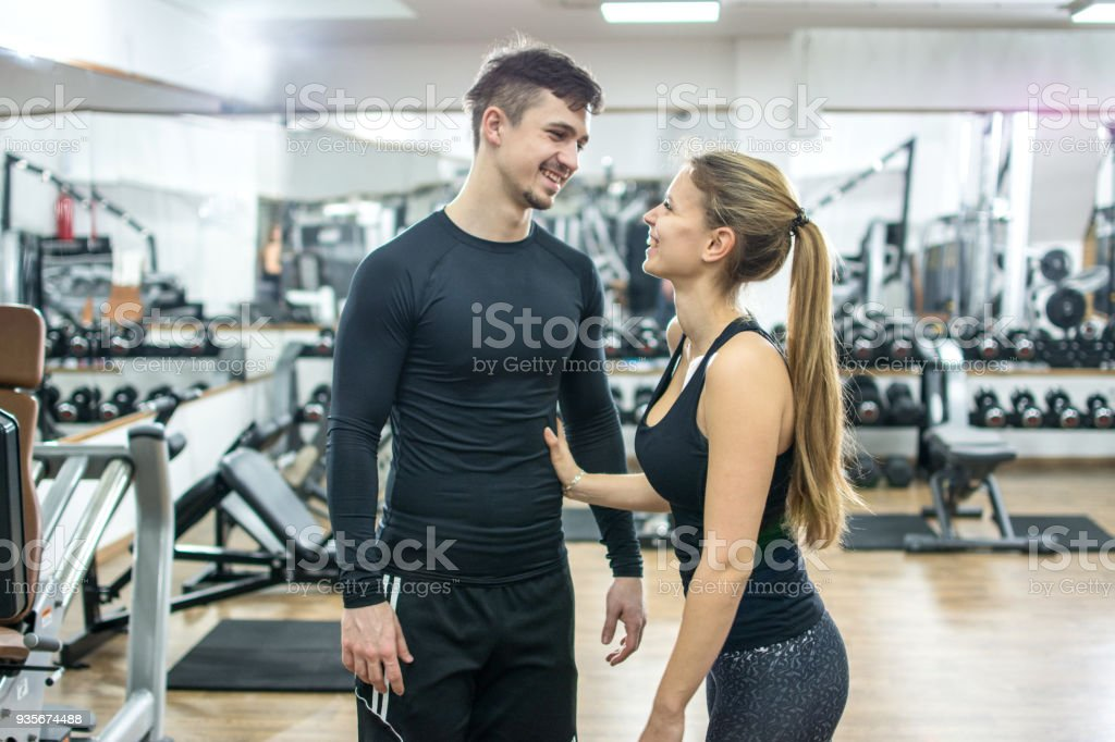 Beautiful young woman and man flirting in gym