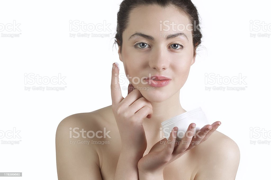 Beautiful young woman appling mosturizer to her face stock photo