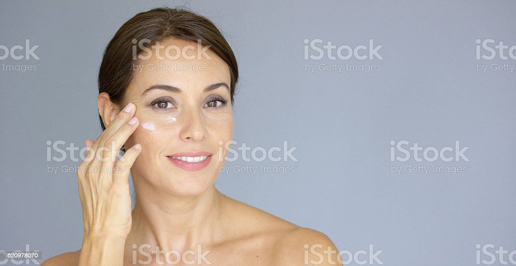 Beautiful young woman applying face cream stock photo