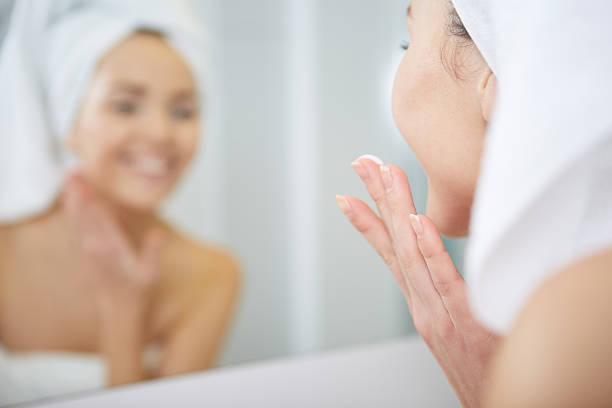 아름다운 젊은 여성 부착으로 얼굴부위 모이스처라이징 cream.Skincare 컨셉입니다 스톡 사진