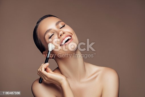 Beautiful young woman applying foundation powder
