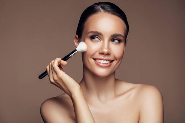 Beautiful young woman applying foundation powder stock photo