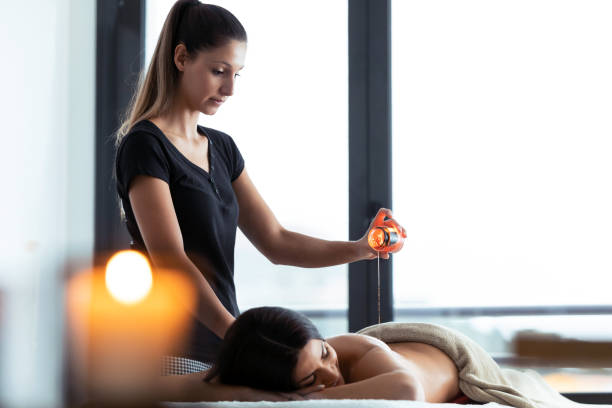 beautiful young woman applying hot wax from a candle for back massage to a pretty woman on the spa center. - mão no chakras velas imagens e fotografias de stock