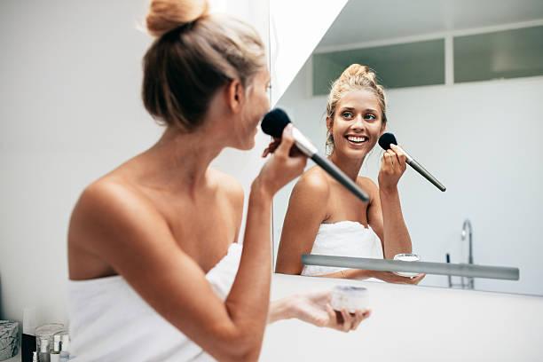 beautiful young woman applying makeup in bathroom - feminine badezimmer stock-fotos und bilder