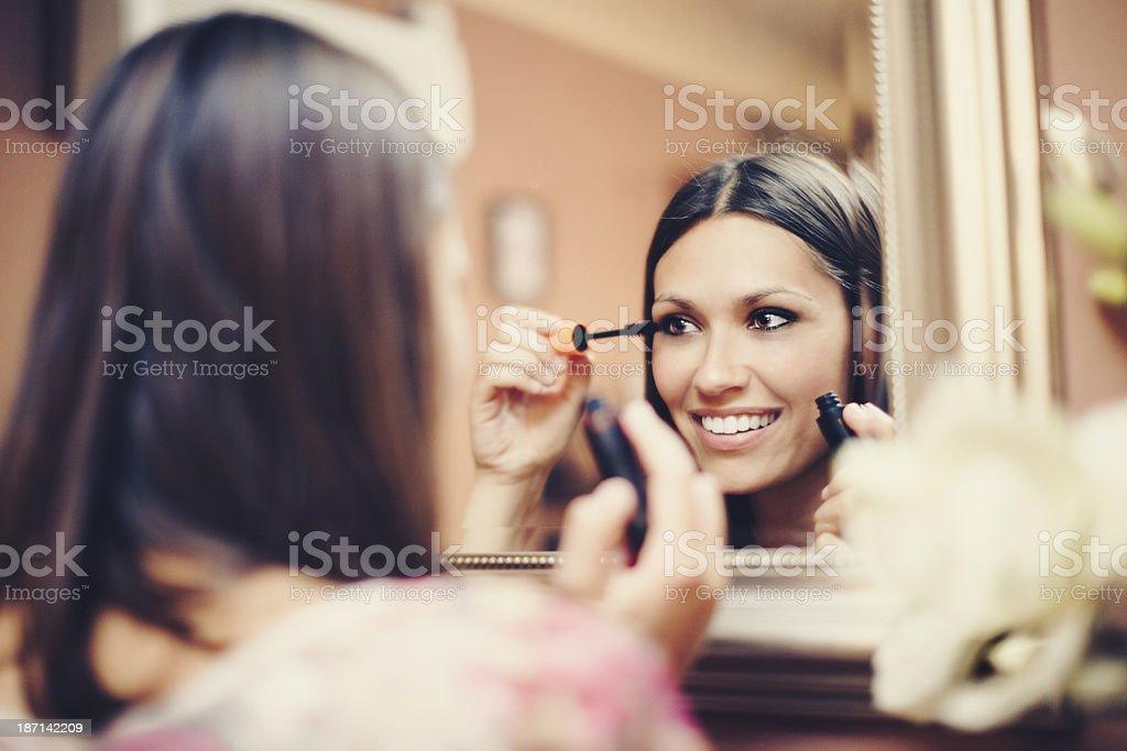 Beautiful young woman applying mascara stock photo
