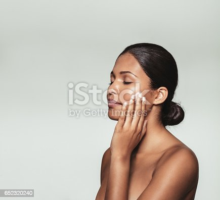 istock Beautiful young woman applying moisturizer to her face 652320240