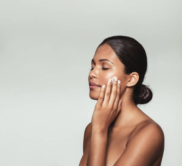 Beautiful young woman applying moisturizer to her face stock photo