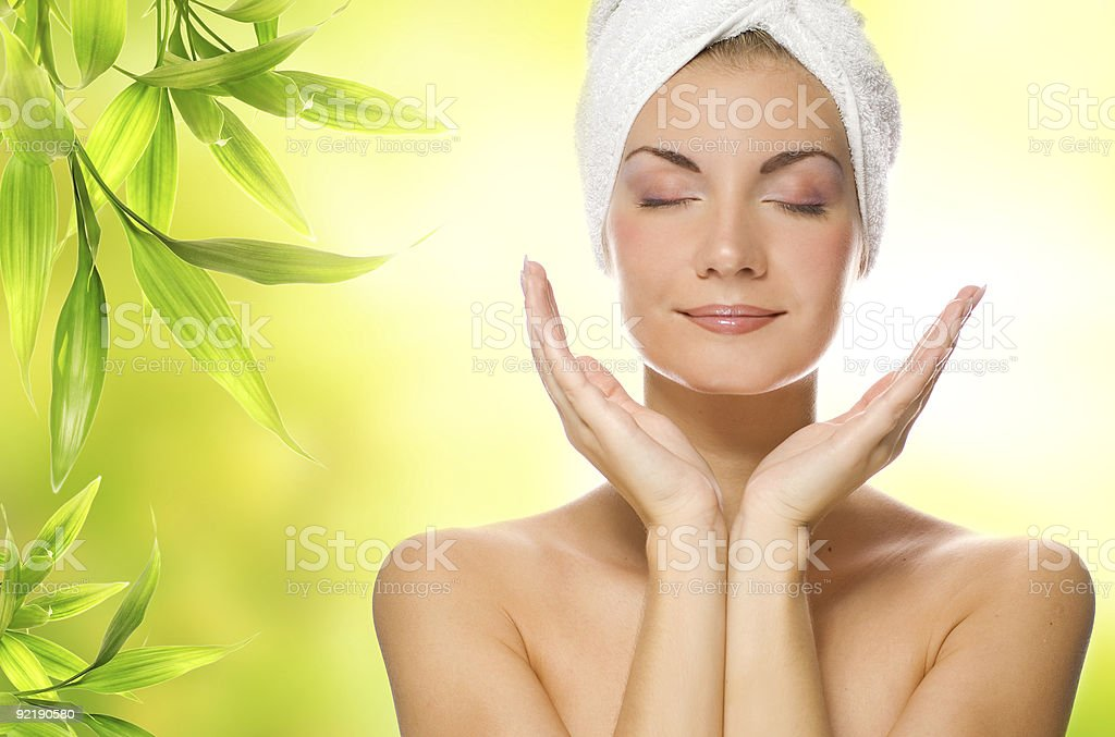 Beautiful young woman applying organic cosmetics to her skin stock photo
