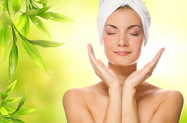 Beautiful young woman applying organic cosmetics to her skin stock photo