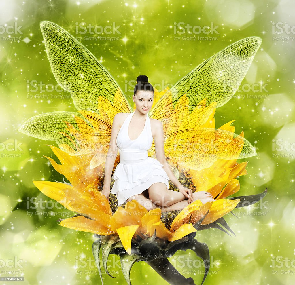 Beautiful young woman as summer fairy on sunflower stock photo
