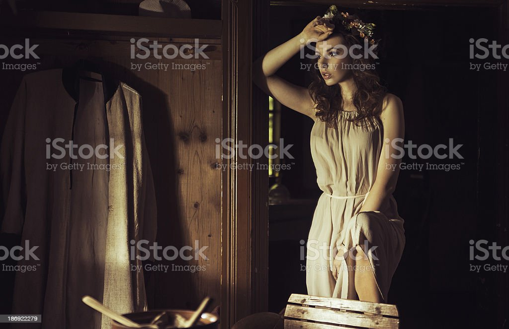 Beautiful young woman at an old rustic cottage royalty-free stock photo