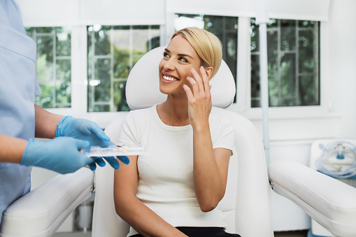 Beautiful and happy blonde woman at beauty medical clinic. She is sitting and talking with female doctor about face esthetics treatment.