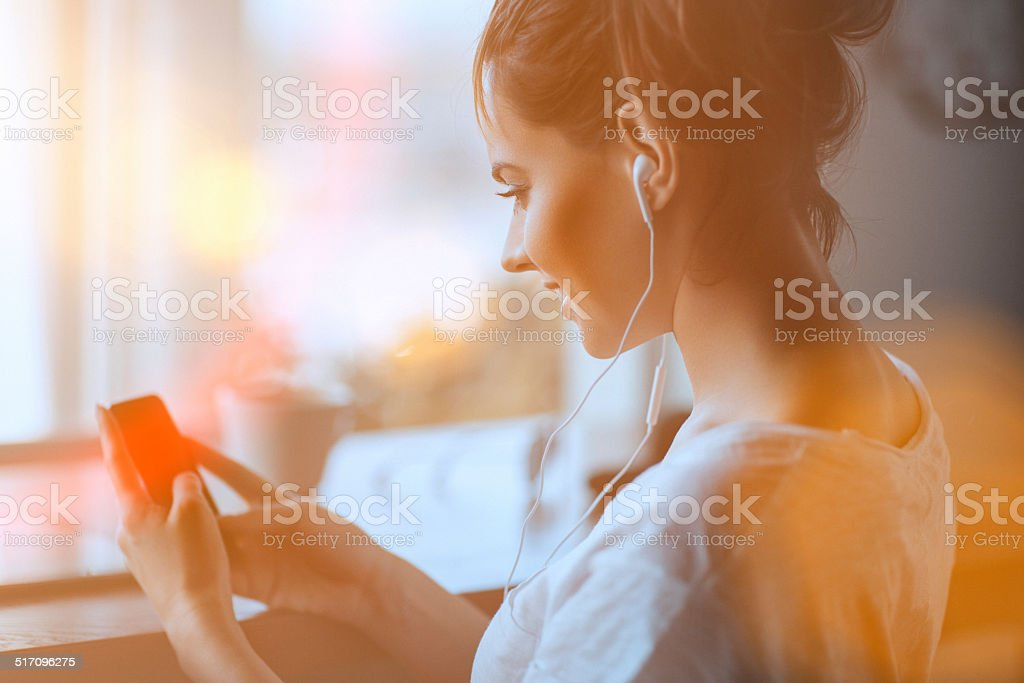 Beautiful young woman at cafe, using mobile phone stock photo