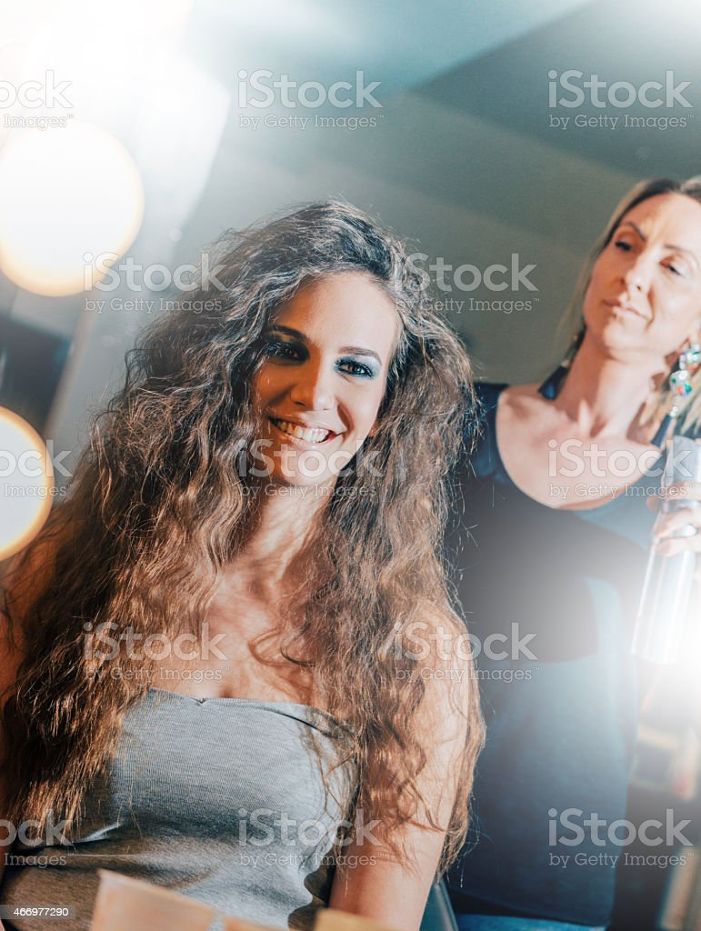 Beautiful young woman with curly hair at hair dresser doing her hair....
