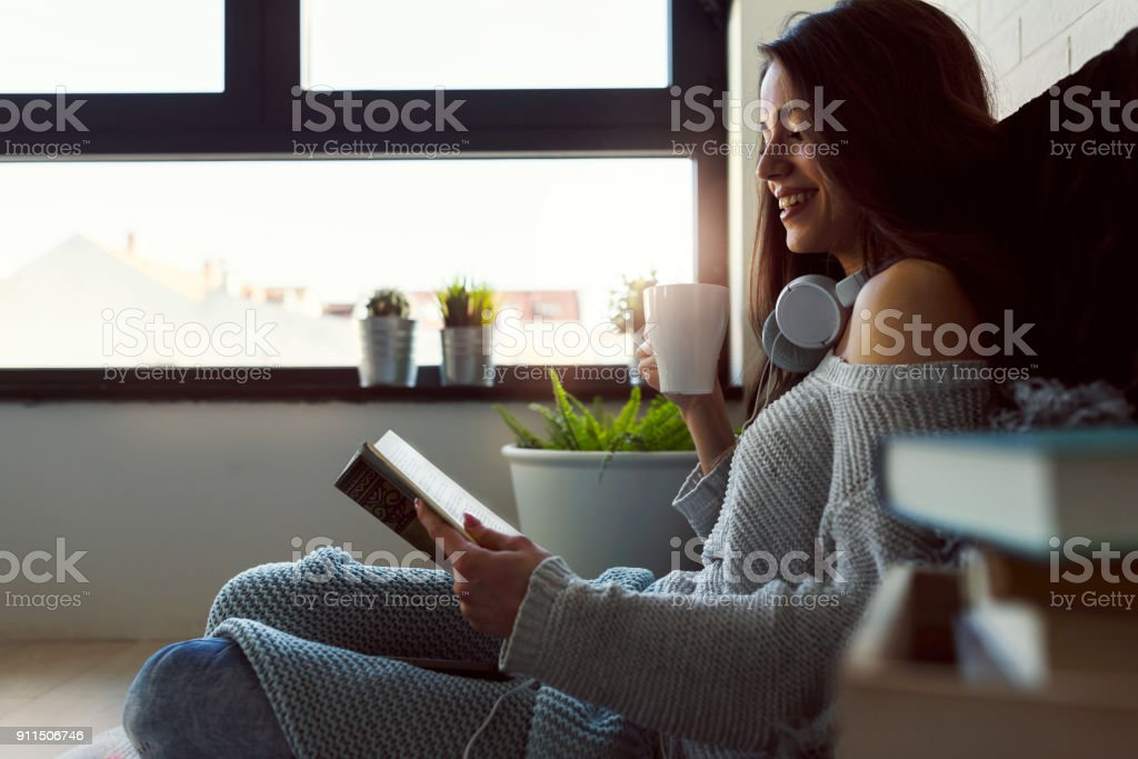 Beautiful young woman at home drinking coffee reading a book stock photo