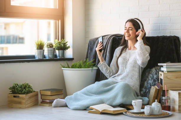 Beautiful young woman at home enjoys listening music stock photo