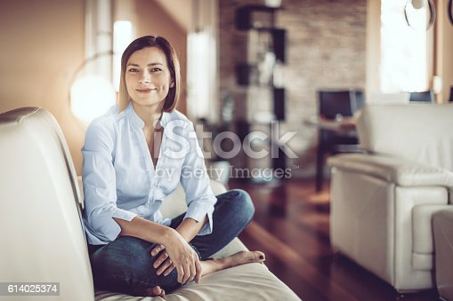 istock Beautiful young woman at home 614025374
