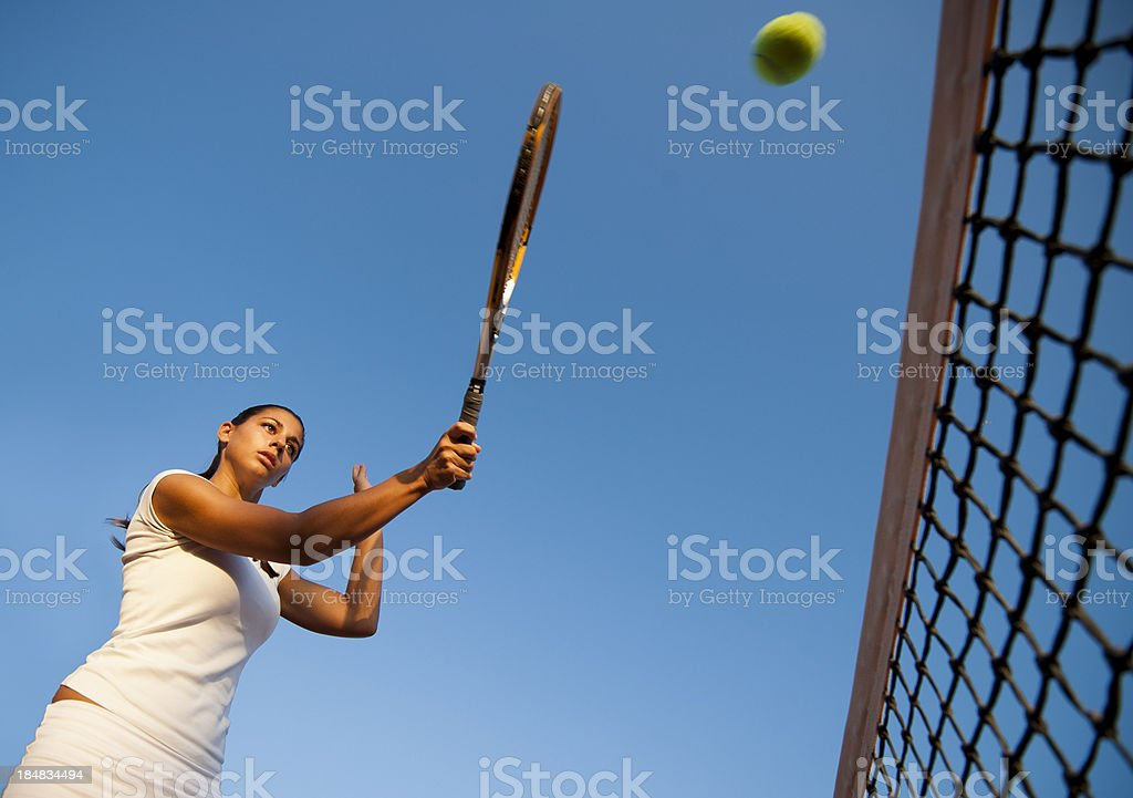 Lower view of female tennis player at volley