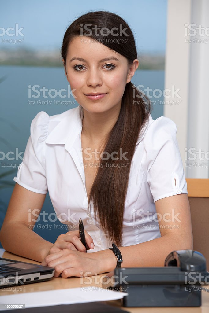 Beautiful young woman at work in office stock photo