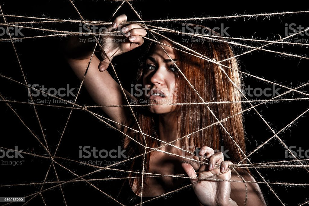 Beautiful young woman behind the interlaced ropes stock photo