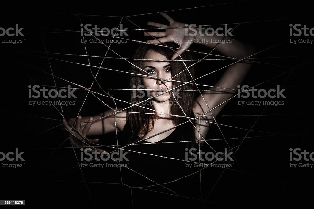 Beautiful young woman behind the net of ropes stock photo