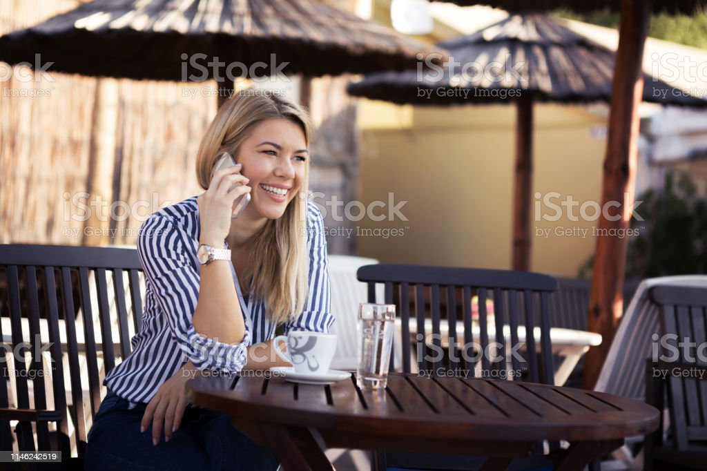 A beautiful young woman blond laughing and talking on the phone while...