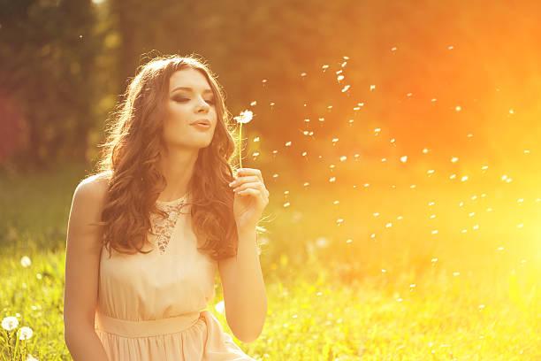 아름다운 젊은 여성 불기, 민들레.  트렌디한 소녀 스톡 사진