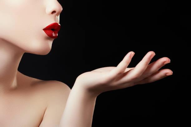 bella mujer que sopla un beso de su mano. modelo con redl oscuro perfecto labios y cuidadas uñas rojo - labios rojos fotografías e imágenes de stock