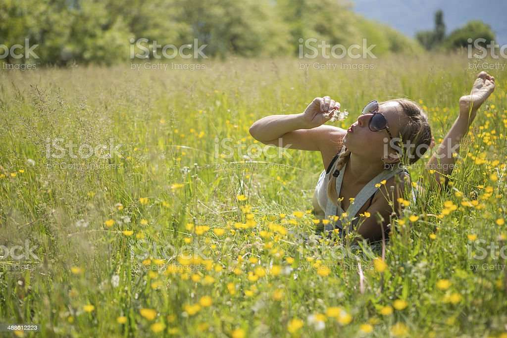 Beautiful young woman blowing Dandelion seeds royalty-free stock photo