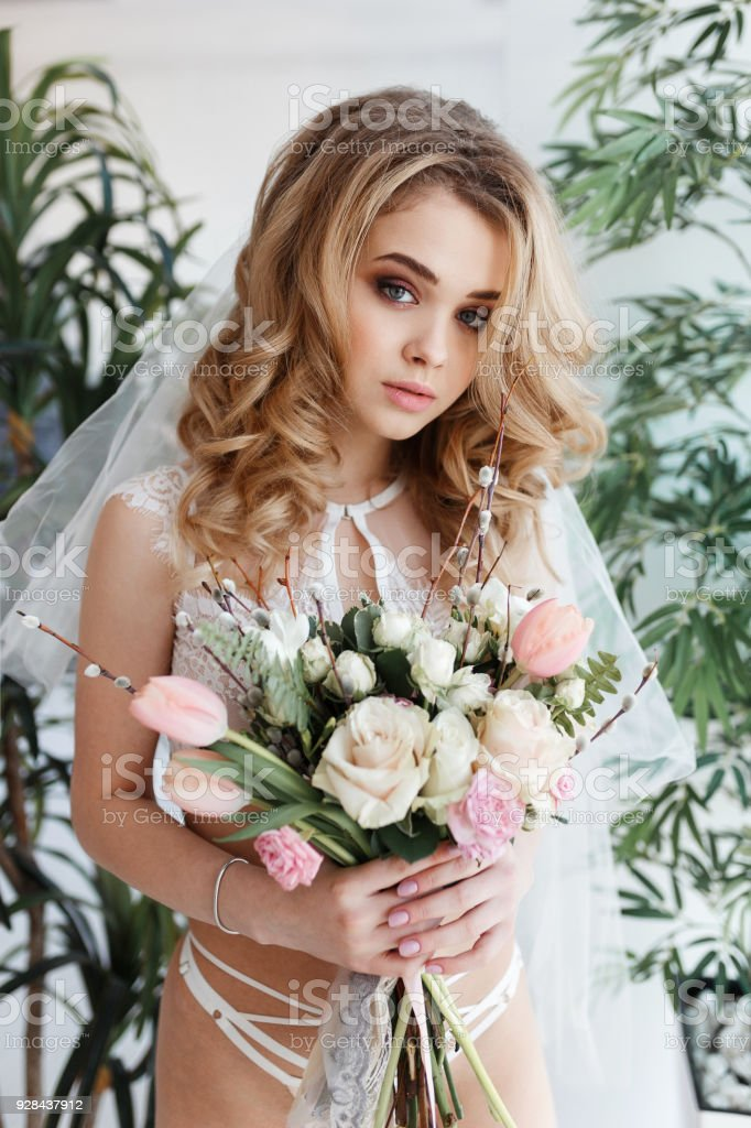 3d68ab983b1 Beautiful young woman bride standing in underwear and white silk veil on a  background of green leaves