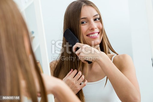 istock Beautiful young woman brushing her long hair in front of her mirror. 868685188