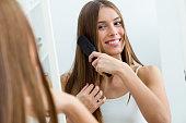 美しい若い女性が彼女の鏡の前で長い髪をかきあげます。