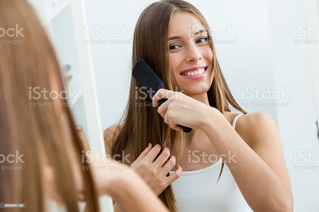 Beautiful young woman brushing her long hair in front of her mirror. stock photo